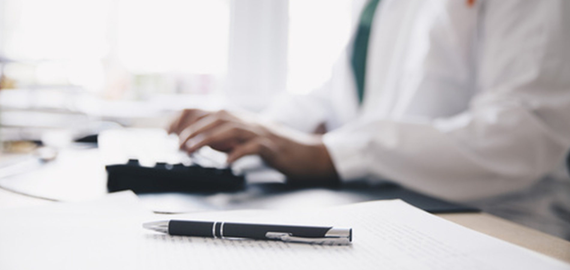 Midsection of male doctor typing on keyboard at office in hospit